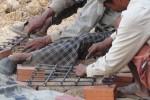 Arbeiter schneiden Eisengitter