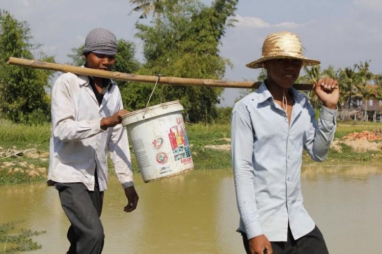 Arbeiter tragen Kübel mit Bambusstange