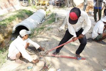 Arbeiter schneiden Eisenstangen