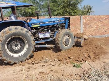 Traktor verteilt die Erde auf unserem Grundstück