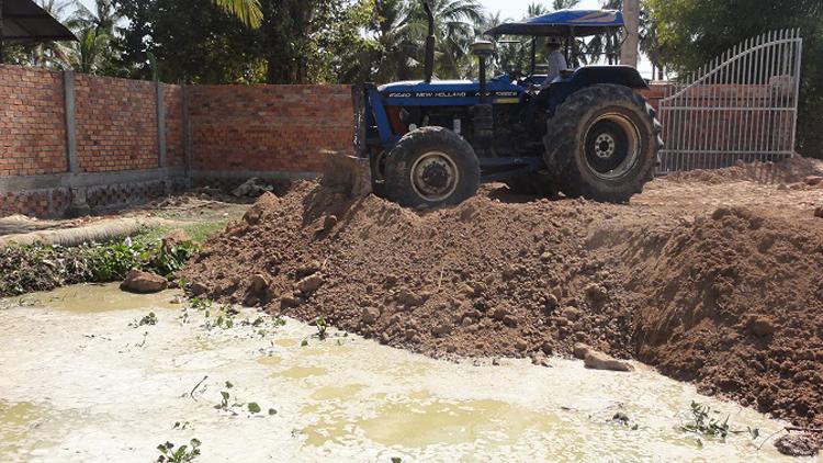 Traktor verteilt das Erdreich auf unserem Grundstück
