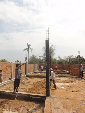 Arbeiter befeuchten die betonierten Säulen
