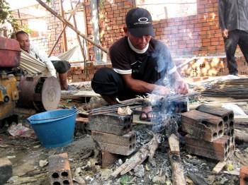 Einer der Arbeiter grillt Fisch