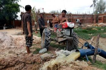 Arbeiter pumpen das Wasser des Fischteichs ab