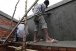 Zwei Arbeiter verputzen die Innenwände