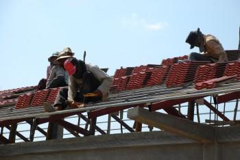 Arbeiter verlegen Ziegel am Dachstuhl