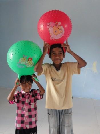 Zwei glückliche Kinder mit Gummibällen
