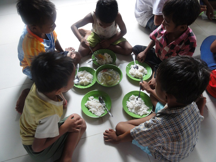 Kinder und Volontäre beim Mittagessen