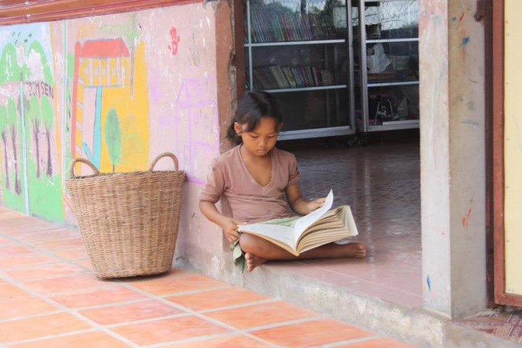Eines der Kinder lernt vor dem Klassenraum